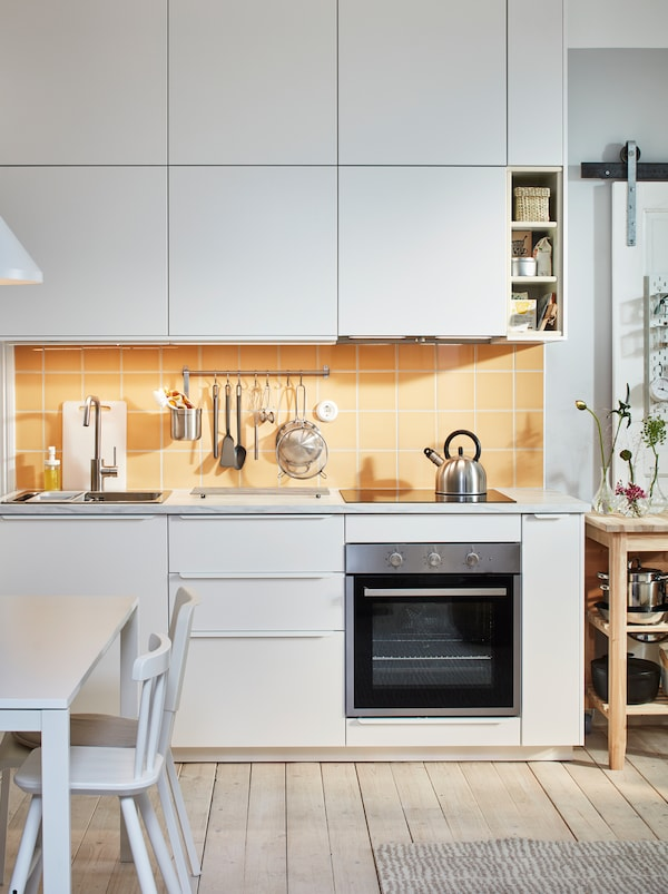 Kitchen worktop with sink, hob and utensils that's framed above and below with rows of cupboards with white VEDDINGE fronts.