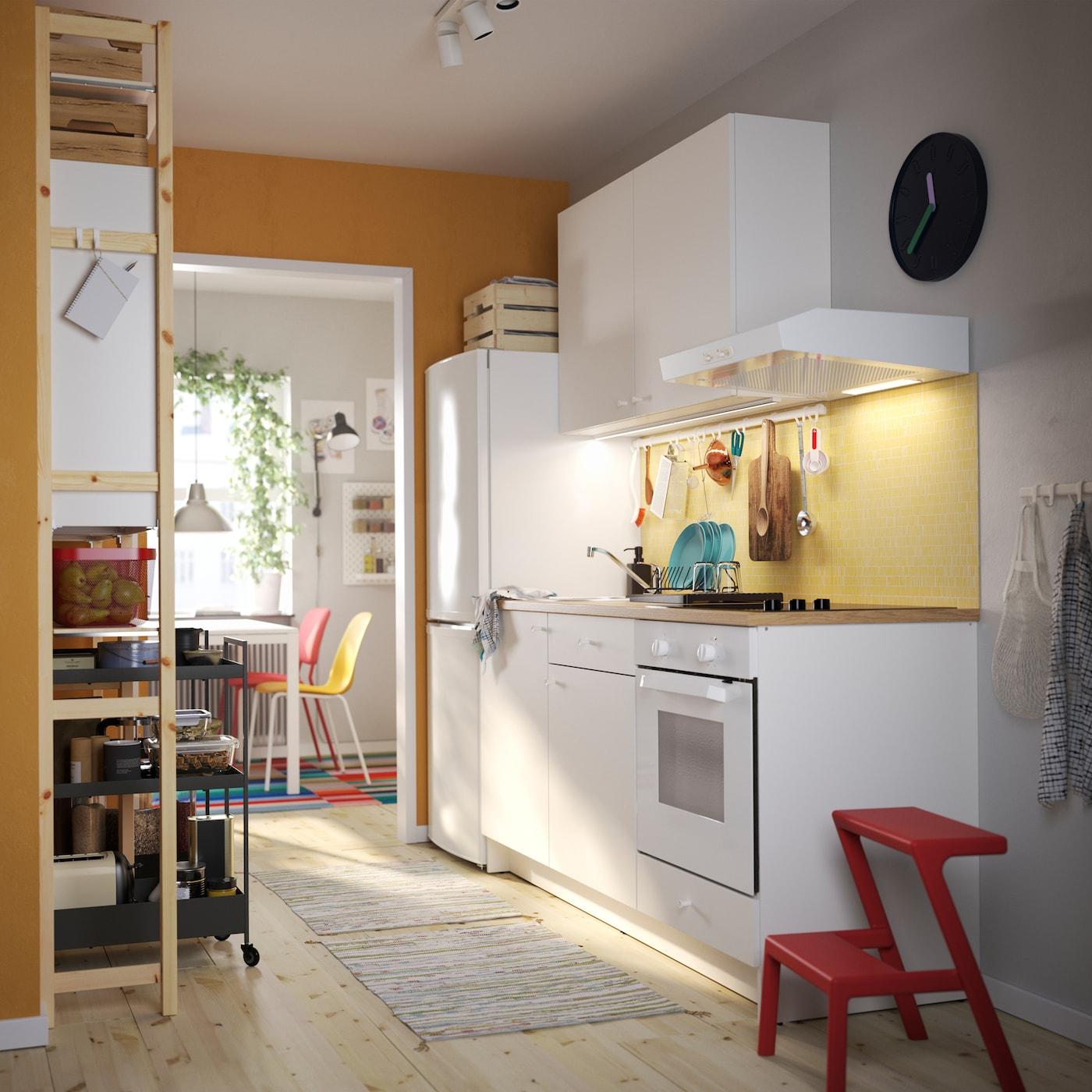 KNOXHULT 诺克胡 白色厨房、红色踏脚凳、松木搁架单元、黑色手推车及五彩缤纷的厨房椅子。