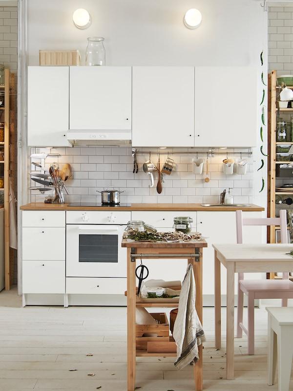 KNOXHULT 诺克胡 厨房,带浅灰色前板,墙面是深灰色镶板,还有一台烤箱。背景是一个用餐区。