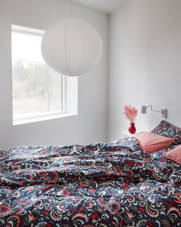 KRATTEN quilt cover featuring a traditional floral pattern in many colours on a dark blue background.