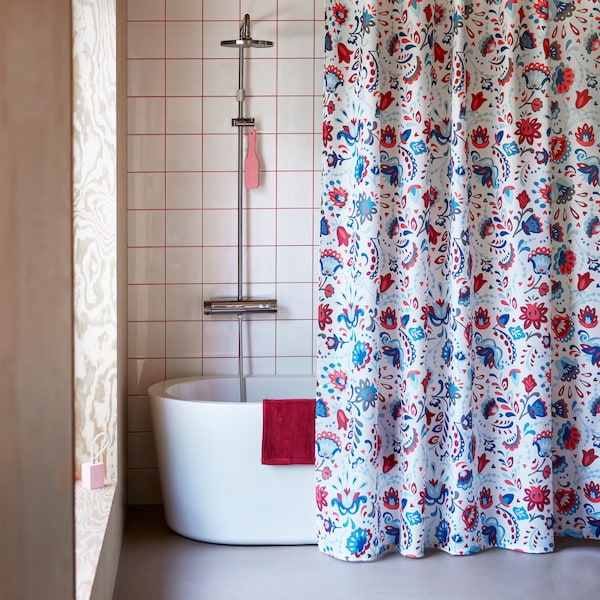 KRATTEN shower curtain featuring a traditional Scandinavian, floral pattern in many colours on a white background.
