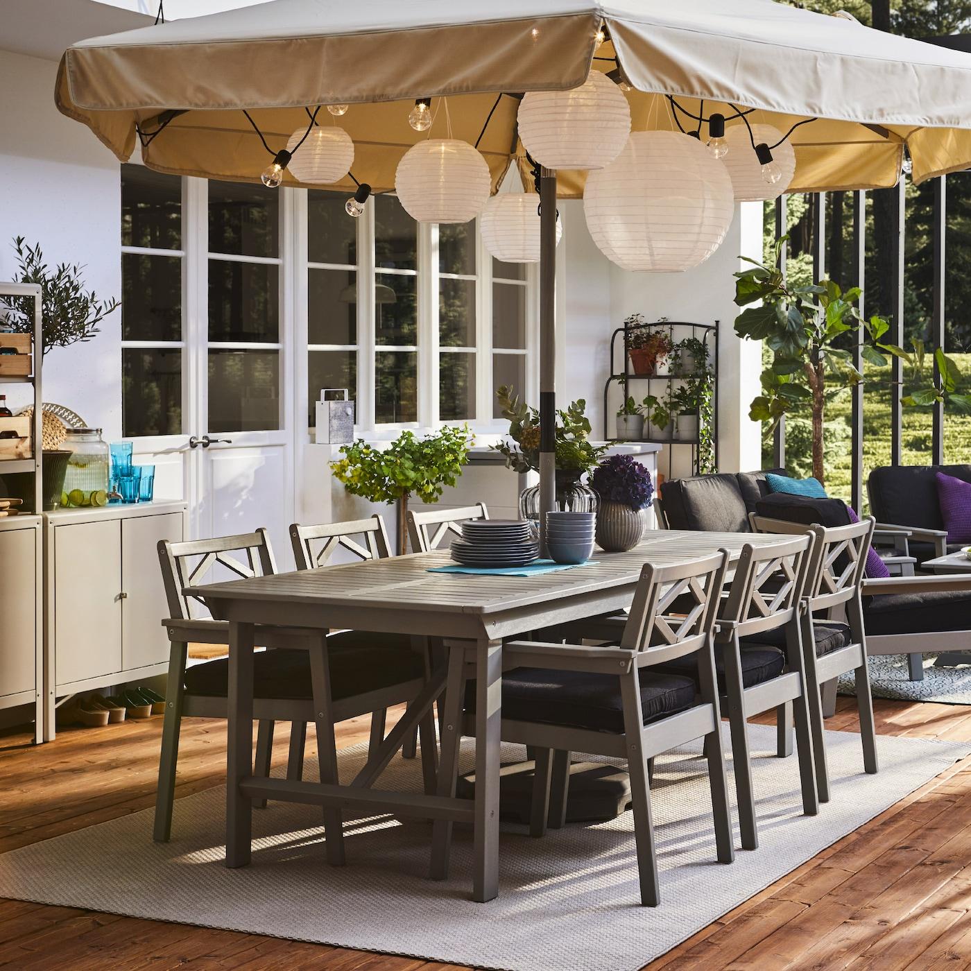 宽敞的露台上有灰色桌子和扶手椅、巨大的阳伞、圆形吊灯和木质地板饰面。