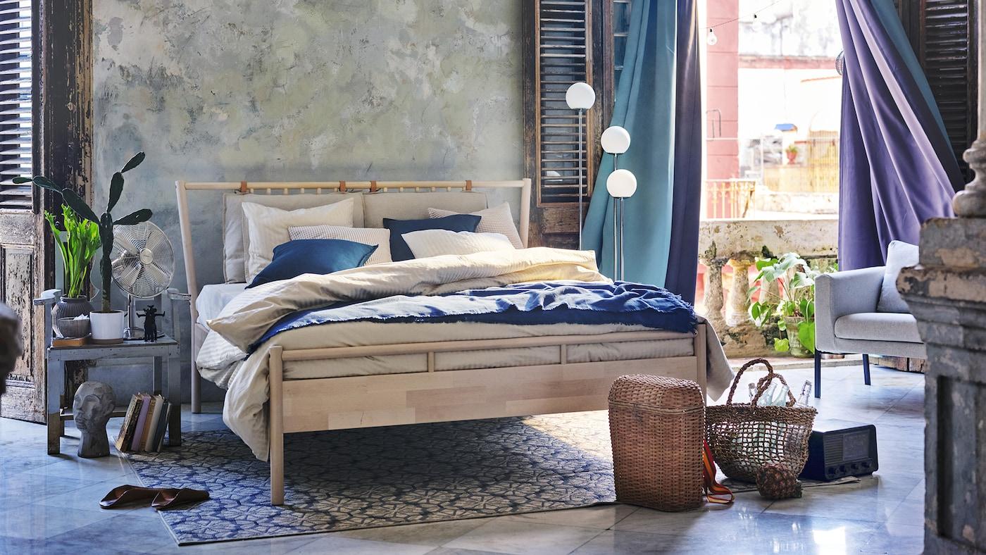 蓝灰色的卧室里,青绿色和紫色遮光窗帘随风飘动。