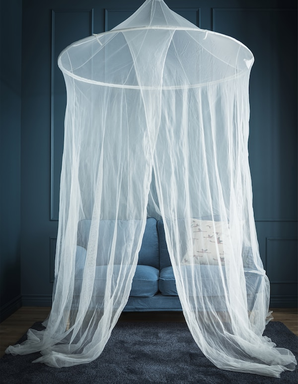 蓝色房间里,蓝色小沙发上方挂着凉篷蚊帐。