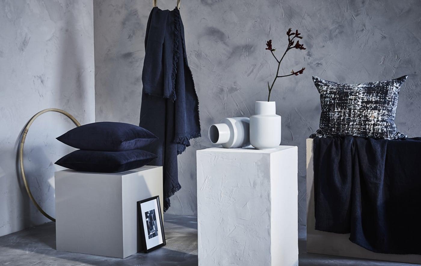 蓝色靠垫和休闲毯摆放在灰白色房间中。