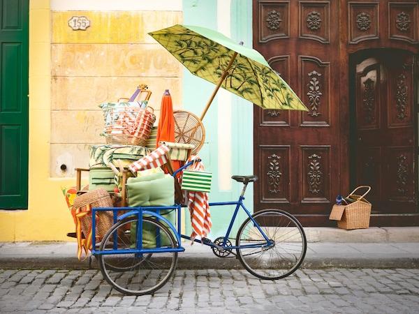 蓝色自行车停放在鹅卵石路上,上面堆放着沙滩风格的宜家 SOLBLEKT 索布列克 系列家具。