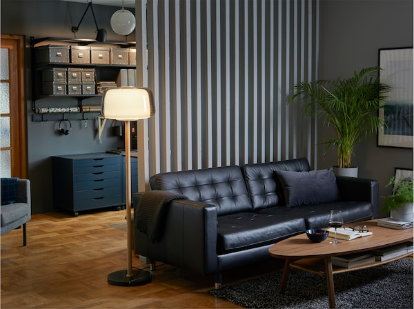 LANDSKRONA black 3-seat sofa in grain leather, a coffee table and lamp in a comfortable, colour-coordinated home workspace.