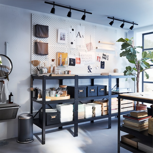 Large black shelving unit, white pegboards with accessories on the wall above and two black ceiling tracks with spotlights.
