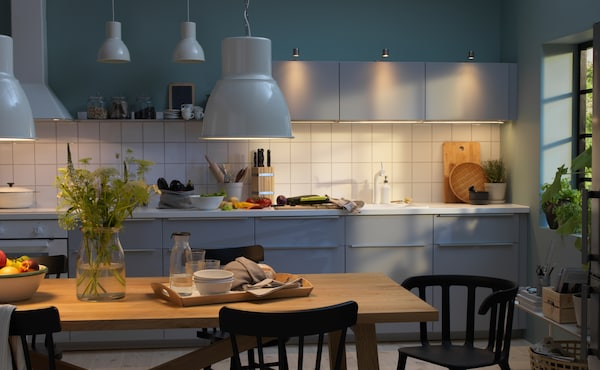 Large kitchen with well-planned lighting, both over the table and by the cabinets.