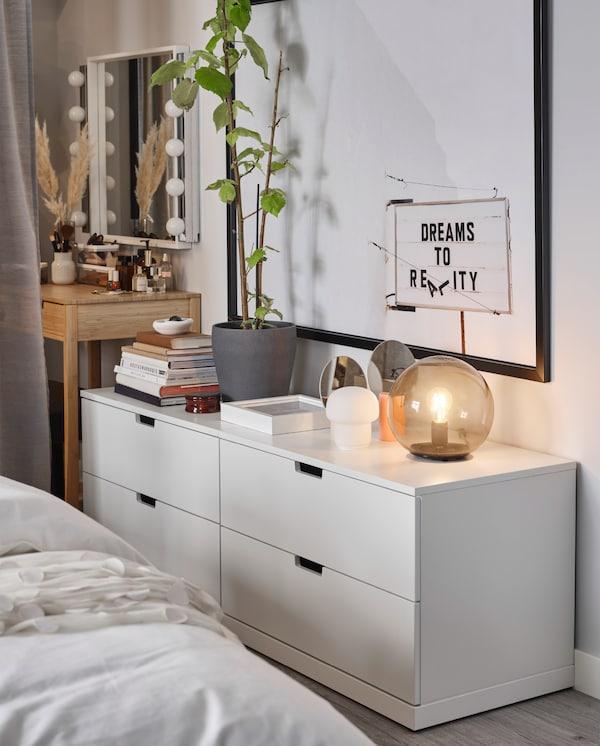 两个白色的 NORDLI 诺德里 抽屉柜靠墙而立。顶层放着台灯、书和装饰品。