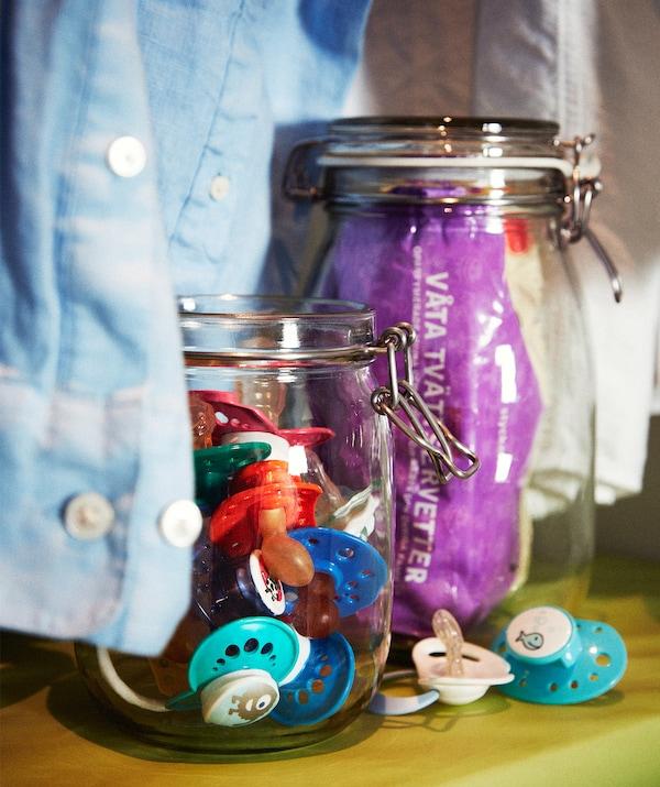 两个玻璃罐立于搁板之上,衬衫衣袖垂于其间。一个玻璃罐中装有安抚奶嘴,另一个则装有湿纸巾。