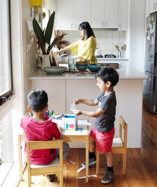 两个孩子在L型厨房前的小桌上做手工,Abeer站在水槽旁。