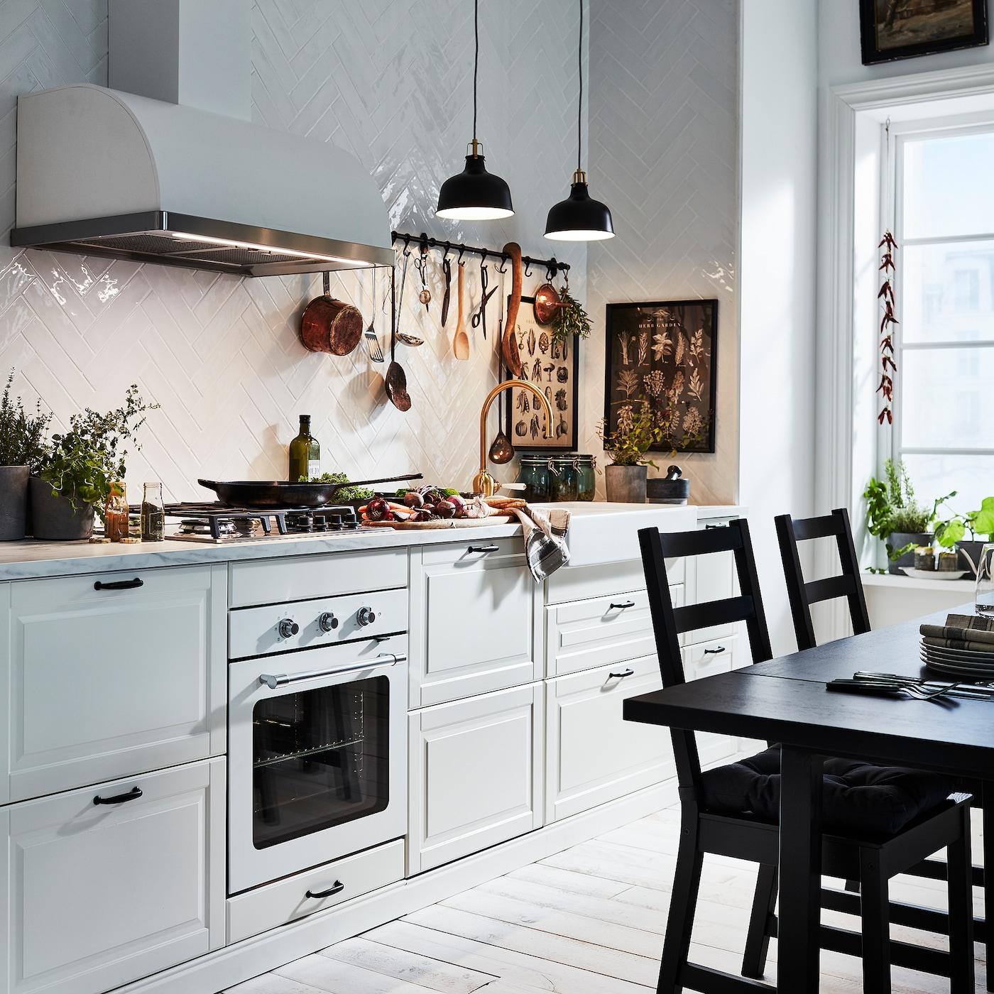 两个黑色吊灯照亮了米白色的 BODBYN 伯德比 厨房。一张黑色桌子旁边摆放着两把黑色椅子。