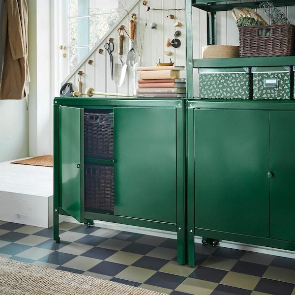 两个绿色的 KOLBJÖRN 科比约恩 柜子放置在楼梯前。其中一个柜子的柜门敞开,里面放有深褐色藤条篮子。