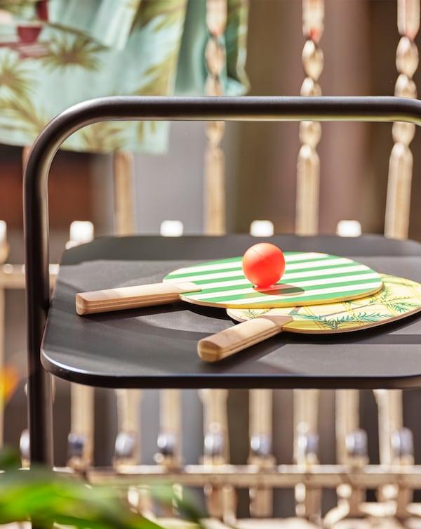 两个绿色和黄色印花球拍,还有一个球,摆放在阳台的黑色桌子上。