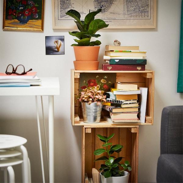 两个木盒子叠放在一起,里面摆满了书和绿色植物。