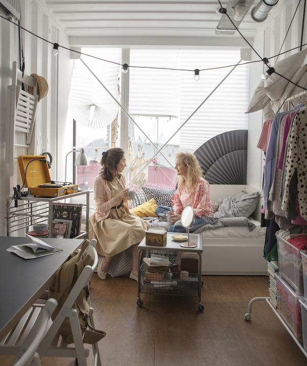两个人坐在一间房内的坐卧两用床上,房间内配备一个开放式挂衣杆和带脚轮手推车,椅子存放在墙壁上。