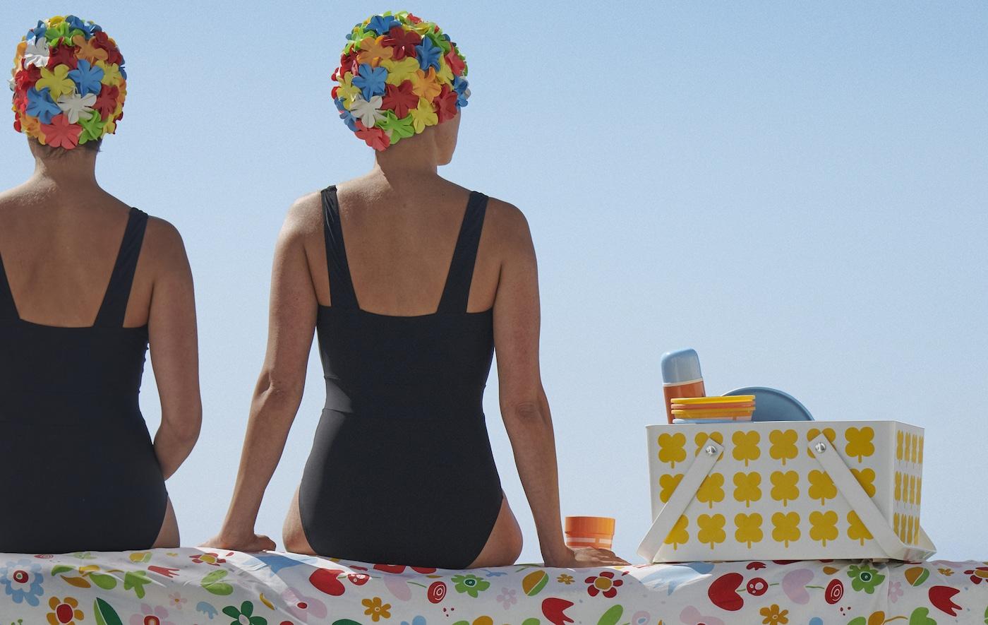 两个身着泳装的人坐在带图案的布料上,旁边是一个野餐盒。