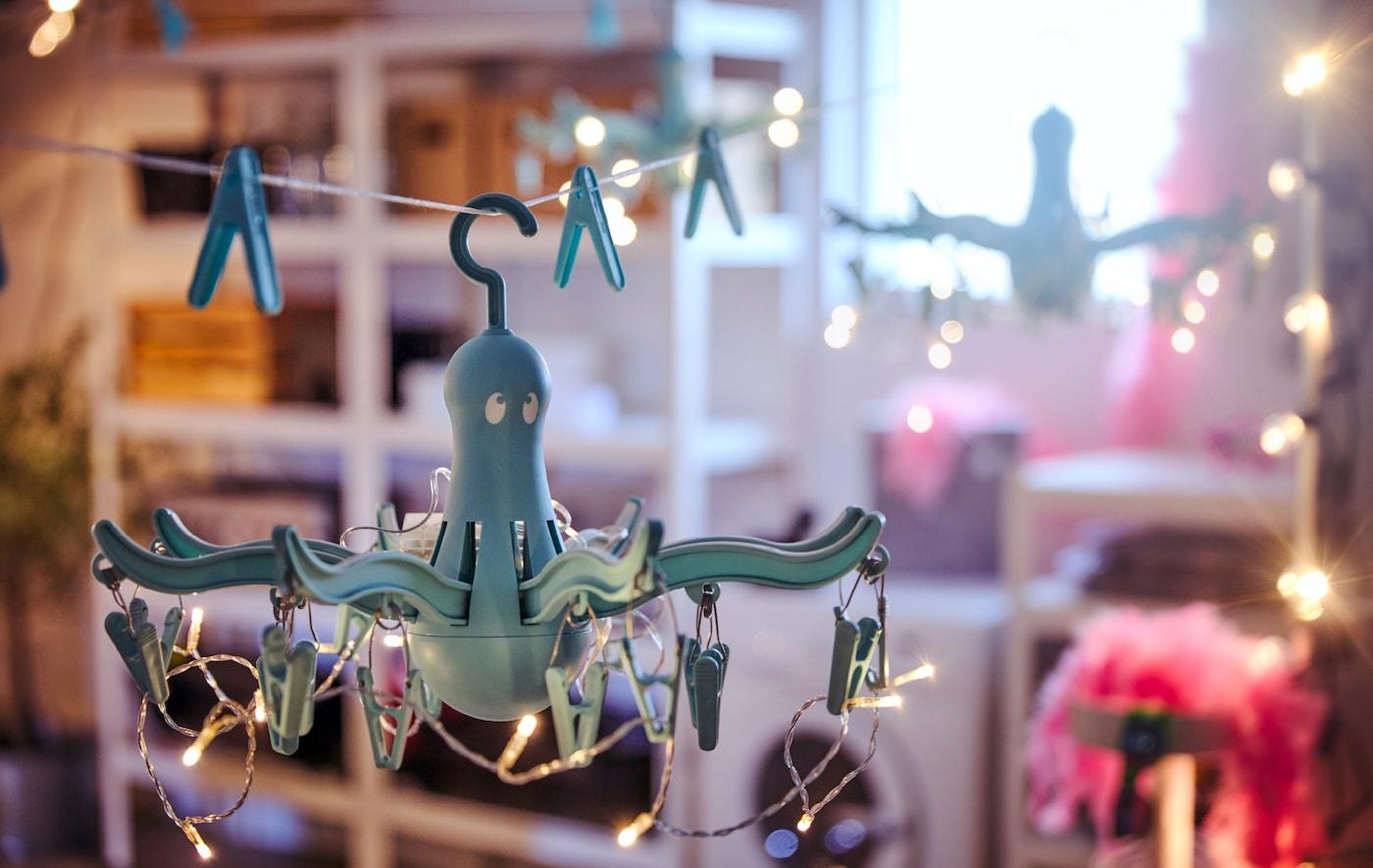 两个由悬挂式晾衣架和照明灯串制成的枝形吊灯,悬挂在放置着洗衣机和各种储物装置的车库内。