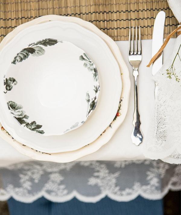 两个造型别致的盘子上叠放着印有花卉图案的碟子,上面摆放着刀叉,桌上铺着白色桌布。