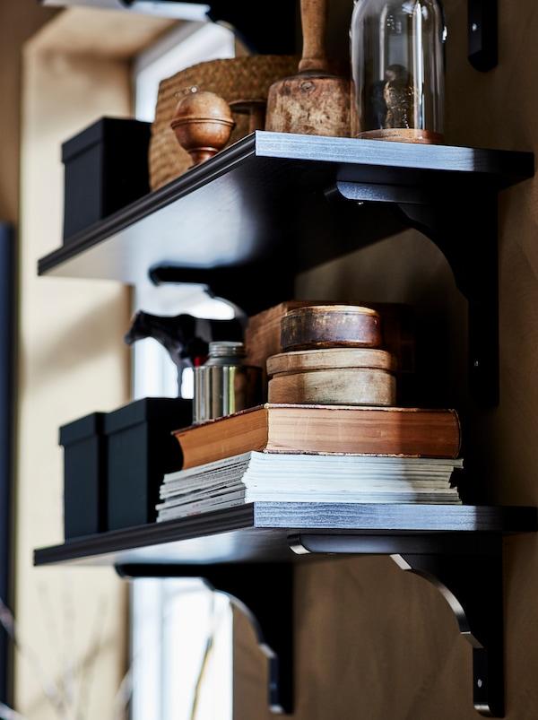 两块固定在墙上的褐色/黑色BERGSHULT 贝利斯胡特/RAMSHULT 拉姆舒特 墙搁板,用于存放和展示书本、储物盒和装饰品。