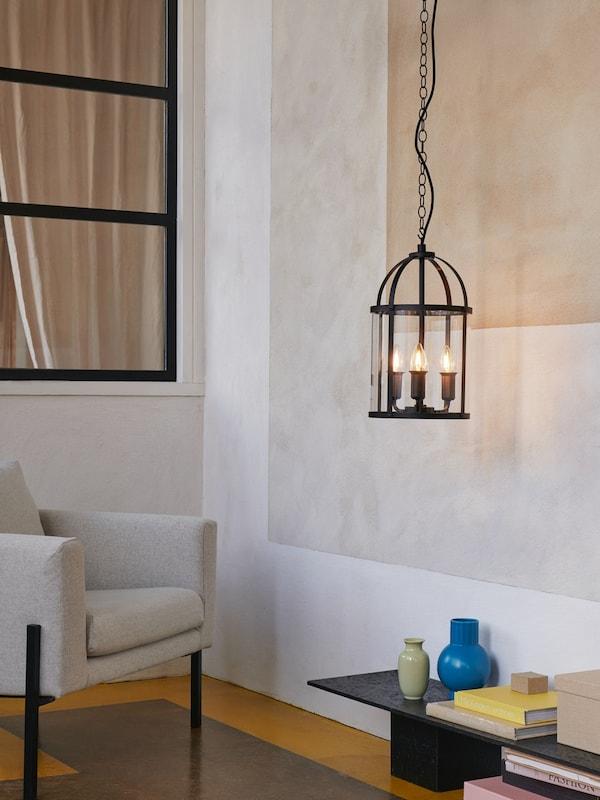 亮着三个枝形吊灯灯泡的黑色传统风格GALJON 加里恩 吊灯悬挂在扶手椅和边桌旁边。
