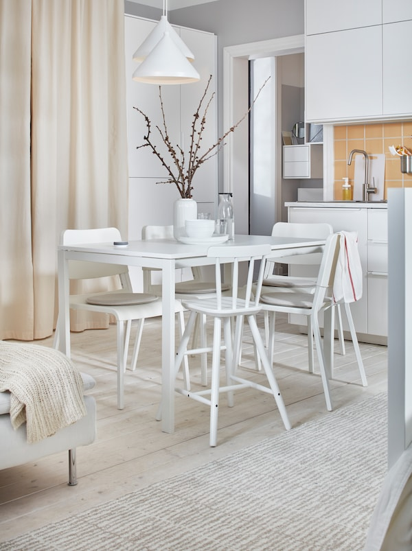 Light-and-white, one-room apartment with a MELLTORP table and TEODORES chairs, in-between a kitchenette and a bed.