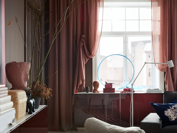 Light brown-pink LEJONGAP curtains are draped with red ribbons and hang by a window where the light shines in beautifully.
