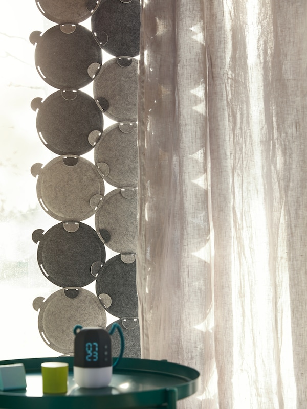 Light streams through a window, partly covered by ODDLAUG sound absorbing panels and an opaque curtain.