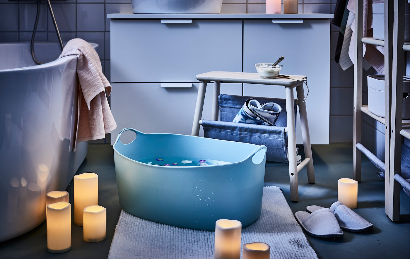 零散摆放的LED阔型烛为浴室提供了情调照明;凳子旁是一个漂浮着花朵的脚盆。