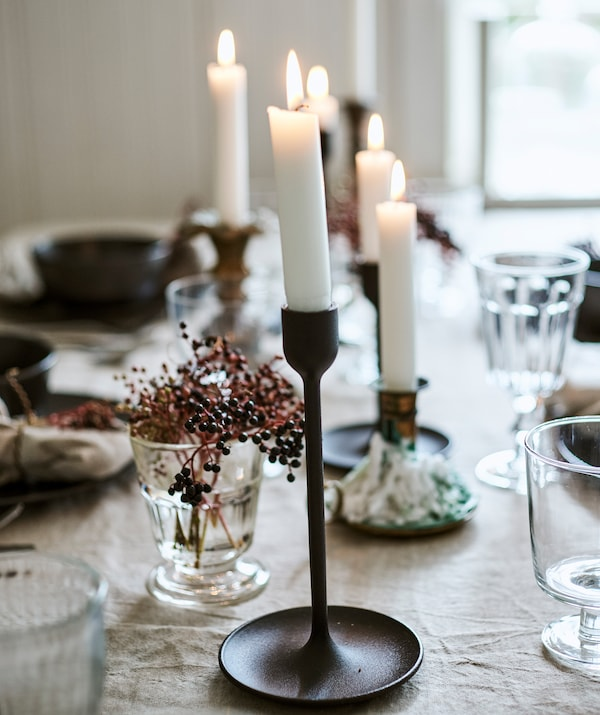 Lit candles in a mix of black and brass candleholders on a table set with linen tablecloth, glasses and berries in a vase.