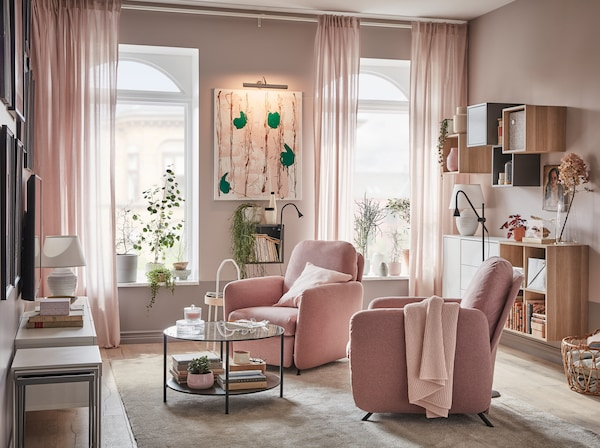 Living room with two EKOLSUND recliners in GUNNARED light brown-pink covers, in front of windows with light streaming in.