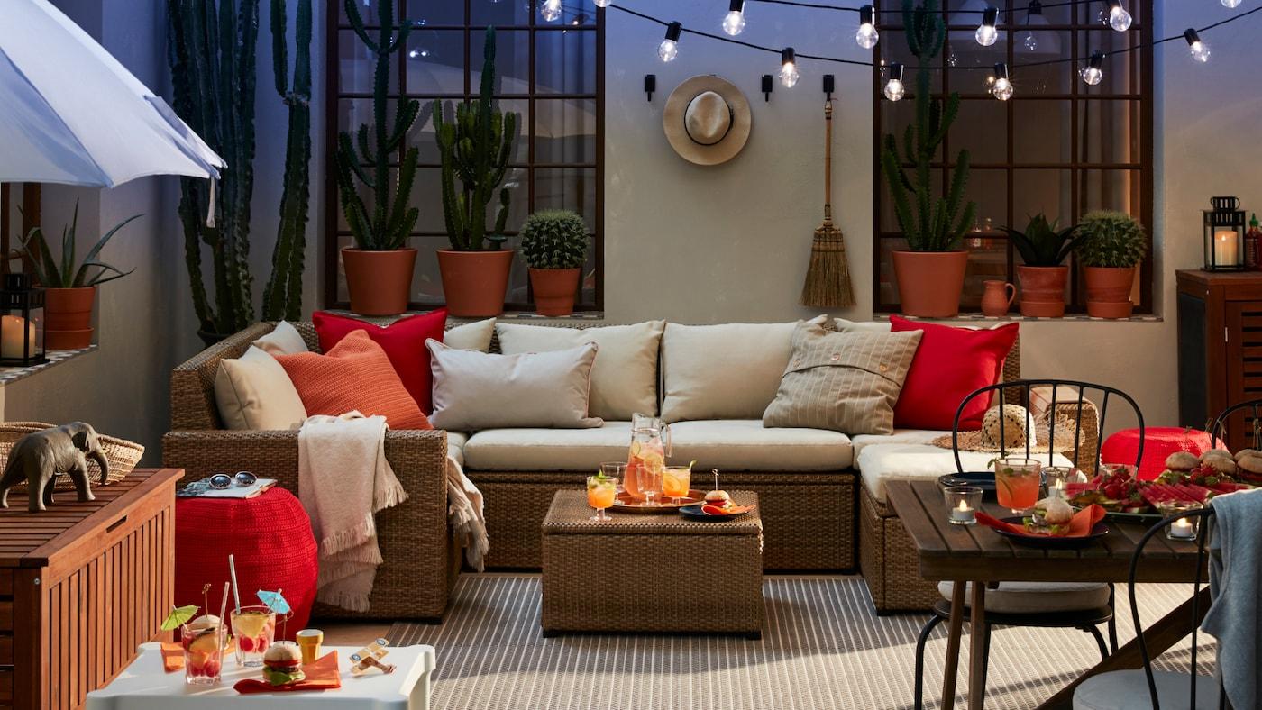 露天庭院上摆放着户外沙发、白色小桌子和几张凳子,还有一套餐桌椅和一把阳伞。