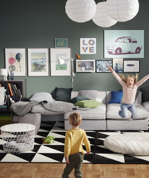 绿色的客厅里摆放着一张巨大的灰色模块沙发,有两个孩子正在玩。