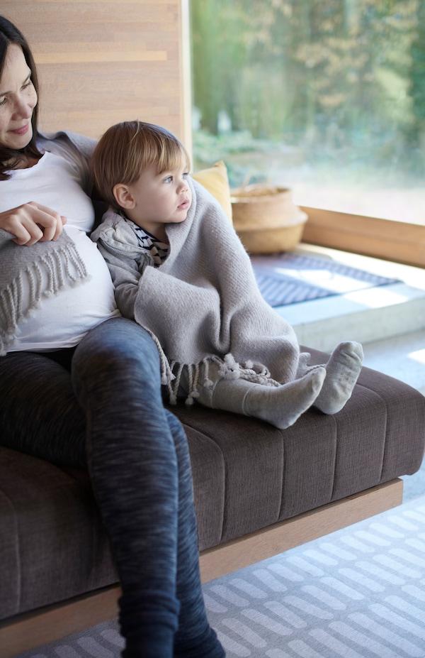 妈妈和年幼的孩子裹着灰色 OMTÄNKSAM 沃姆安克萨姆 羊毛休闲毯,紧挨着坐在沙发上。