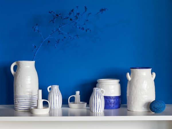 Many GODTAGBAR vases made in stoneware and hand-painted in white and blue, as well as a candlestick in the same series.