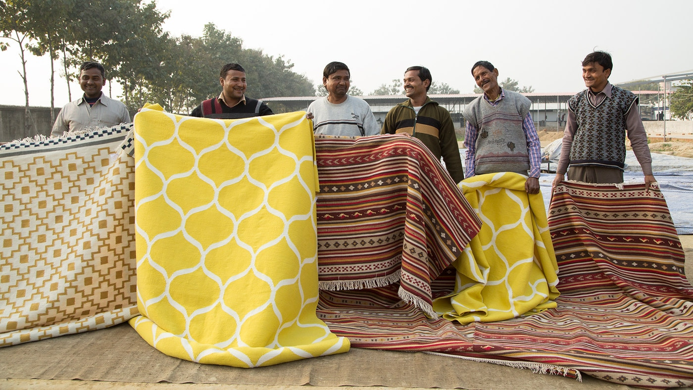 Men holding a selection of hand-woven rugs.