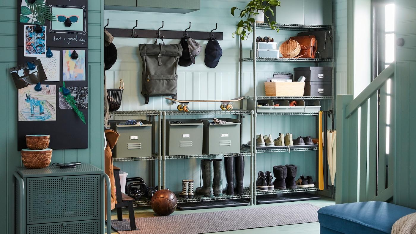 门厅摆放着OMAR 奥马尔 搁架,上面放着鞋子、靴子和金属REJSA 雷萨 储物盒;墙上有两排PINNIG 佩尼格 三头钩架。