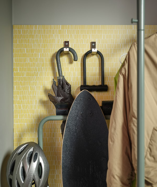 门厅里安装的 LYSEKIL 莱西克 带挂钩防溅板上挂着雨伞和自行车锁。NIKKEBY 尼克比 晒衣架上挂着滑板。