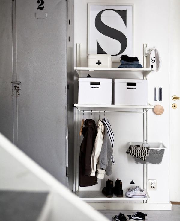 门厅里设有一个白色搁架单元,上面摆放着储物盒,下面是一条较低的挂杆和金属丝篮。