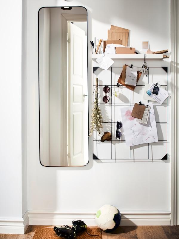 门厅墙壁上有一面长镜子,一个搁板和一个黑色的SÖSDALA 索斯达 钢制记事板,上面用夹子展示着各种便签纸。