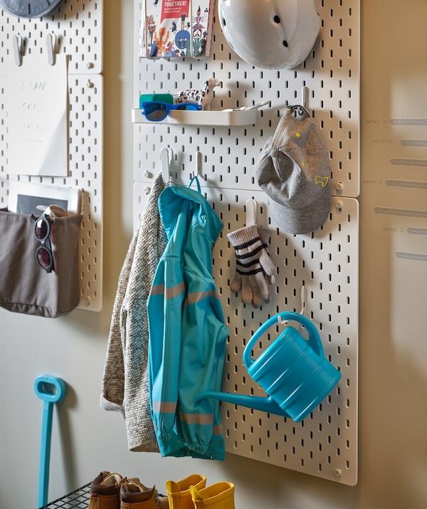 门厅墙的不同高度处安装着 SKÅDIS 斯考迪斯 钉板,钉板上放着玩具、衣物和配件。