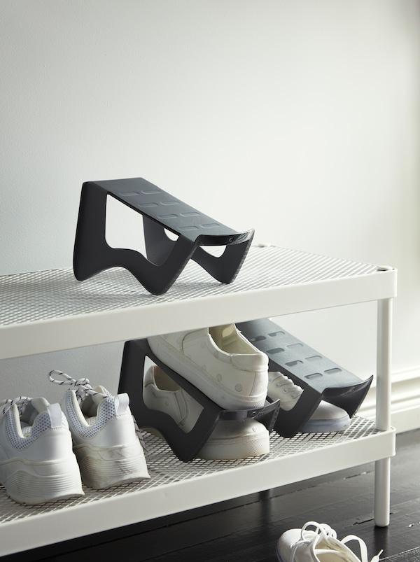 门厅上的一个白色鞋架,上面有两块网状搁板,以及三个节省空间的灰色MURVEL 穆沃尔 塑料鞋储藏件。