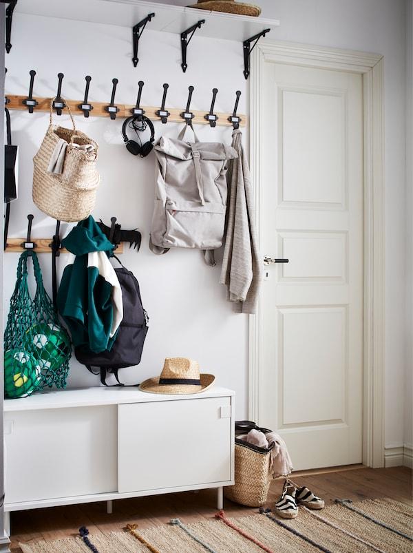 门厅上有一排挂钩,挂放着外套和书包,上方有一个宽储物搁板,下面是白色的MACKAPÄR 马凯帕 附储物格的长凳。