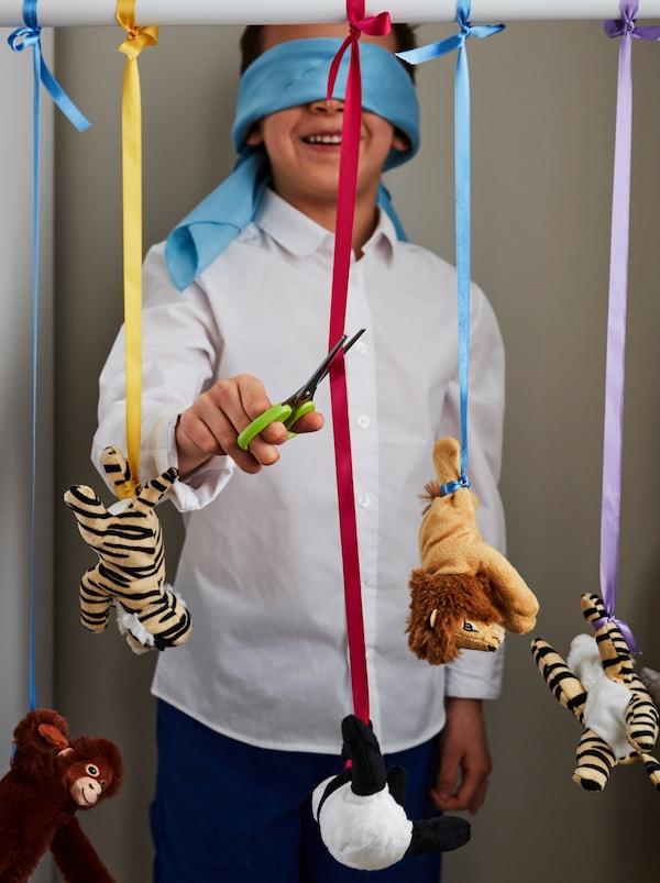 蒙住眼睛、面带笑容的男孩站在一排用装饰带悬挂固定的 DJUNGELSKOG 尤恩格斯库格 毛绒玩具旁,试图用 MÅLA 莫拉 剪刀剪下一个玩具。