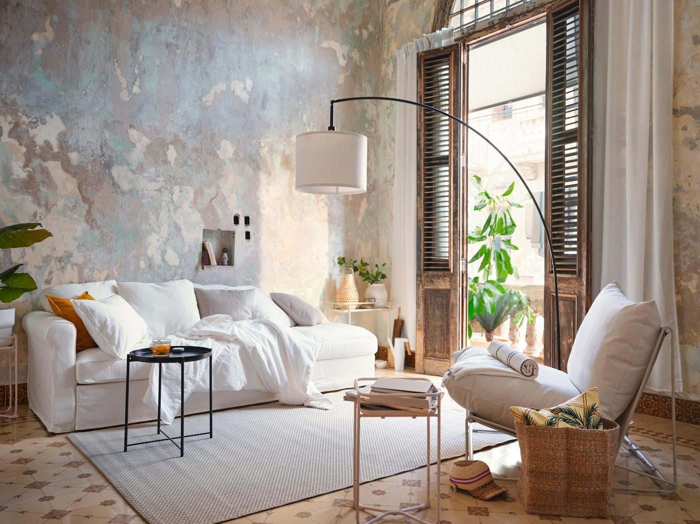 米灰色的空间内摆放着白色沙发、散落的软垫、黑色边桌和白色休闲椅。