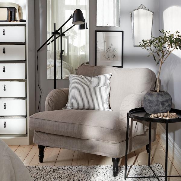 米灰色扶手椅、黑色落地灯、条纹垫套、黑色托盘桌和白色地毯。
