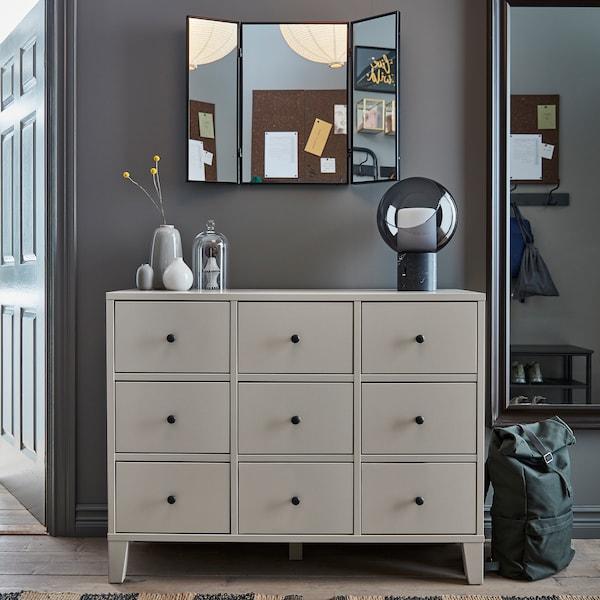 米色 BRYGGJA 布吕格亚 抽屉柜、装饰台灯、全身镜、壁挂式镜子和绿色背包。