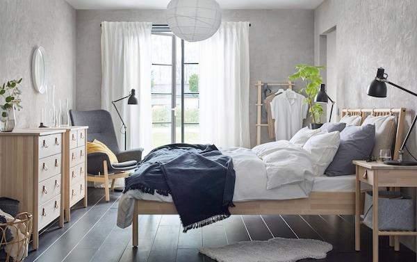 米色和灰色卧室里摆放着实心桦木制成的 BJÖRKSNÄS 约纳斯 床、床边桌和五斗抽屉柜。