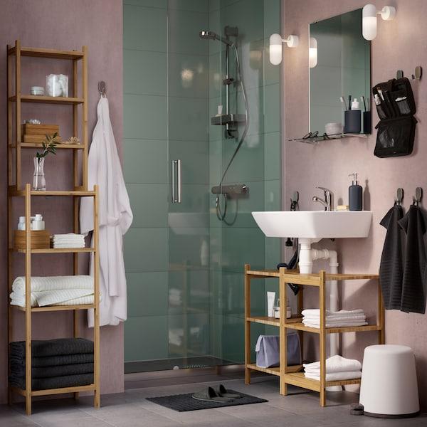米色和灰色浴室里摆放着 RÅGRUND 罗格朗 洗脸池/转角搁板和竹制搁架单元。